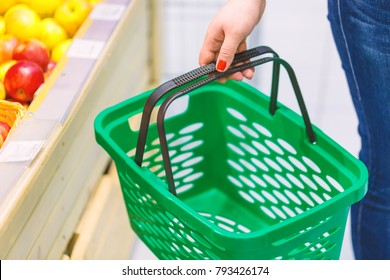 Women holding empty green shopping basket near fruits window in the supermarket. Shopping concept