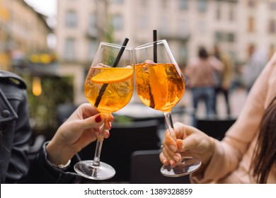 Women holding glasses of summer aperol cocktails and toasting. Lifestyle concept. Outdoors. Traditional Italian aperitif.