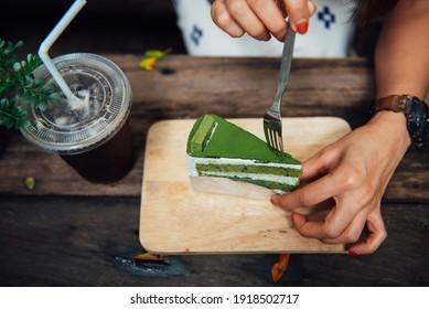 Frauen, die im Urlaub im Café einen grünen Teekuchen halten.