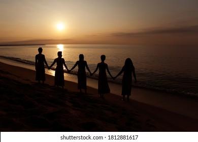 Women holding hands at sunrise