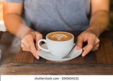 Women holding a hot white cup of coffee latte in hands on wood table in coffee shop.