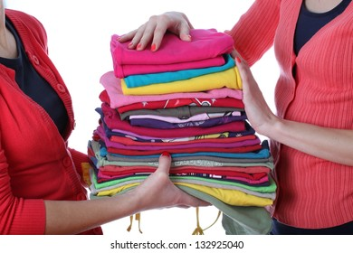 Women holding pile of ironed and colorful clothes