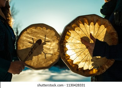 Women holding and playing their sacred drums outdoors in the wintertime
