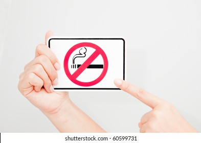 """A women holding and pointing at a """"no smoking"""" sign."""