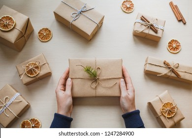 Women holding present laid on a wooden table background. Christmas holiday concept