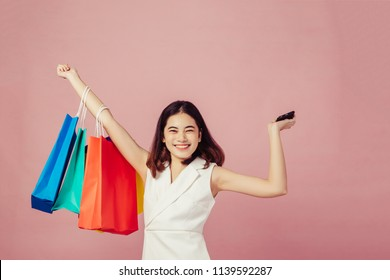 Women holding shopping bags looking up to the side on pink background at copy space.she is using smart phone shoping online ,ecommerce.