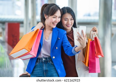Women holding shopping bags and looking at smart phone after enjoyed shopping. Looking for something or take a photo selfie.