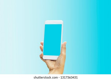Women holding smartphone in hands with blue screen on bright blue-white pastel background. With concept of technology and simplicity and convenience,with empty copy space and for text and image