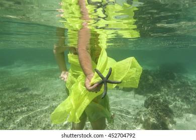 WOMEN HOLDING STARFISH WITH YELLOW SARONG / WATER STAR / FIJI