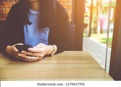 Women holding and using smartphone on wooden table in restaurant.