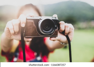 Women holding vintage camera,female tourist taking photos at flied nature background,selective focus.