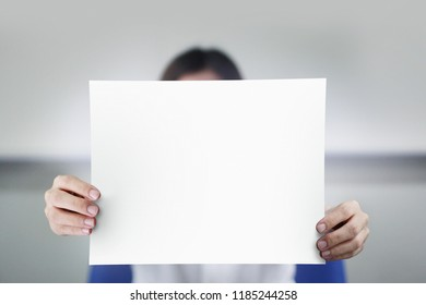 Women holding white empty paper at office.