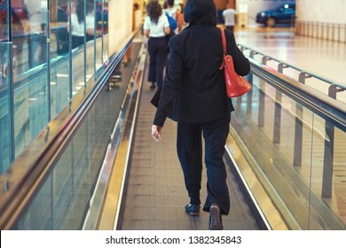 Women at horizontal escalator covered. Moving walkway, moving sidewalk, moving pavement, autopedescalator, walkalator, travelator, horizontal escalator, slidewalk, or moveator at an airport. Toning.