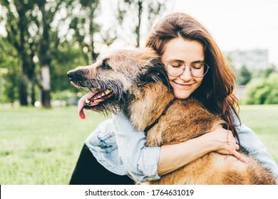 Women hugging dog in the summer park. Cheerful lady with long dark hair in blue jacket hugs and strokes friendly old dog sitting on lush green meadow of public garden on nice day.