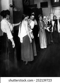 Women immigrants undegoing a physical examination, Ellis Island, New York. ca. November 1910.