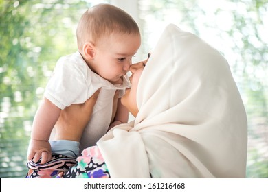 Women with an islamic scarf holding a gorgeous toddler