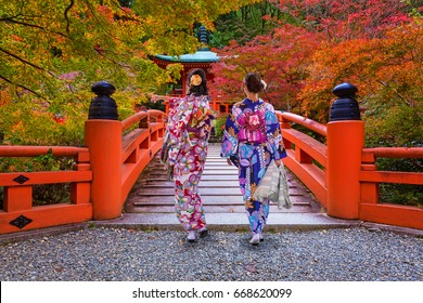 Women in kimonos walking at the colorful maple trees in autumn, Kyoto. Japan