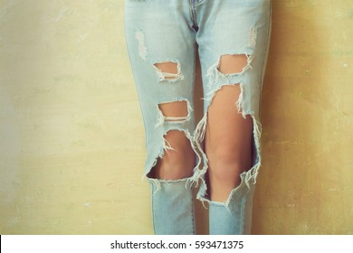 Women knees in jeans close to the studio, holes in jeans, fashion clothing. Hips and knees in fashionable jeans. Girl in jeans advertising