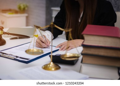 Women lawyer working with contract papers and wooden gavel on tabel in courtroom. justice and law ,attorney, court judge, concept.