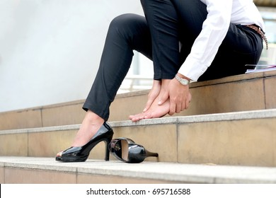 Women with leg cramps and ankles from high heels. She sat on the stairs holding her leg. Health concept