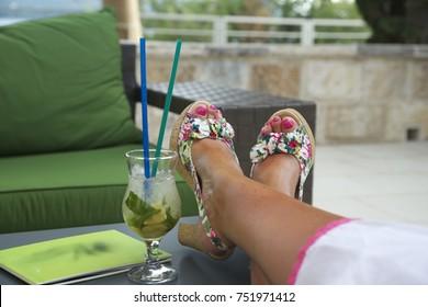 Women legs near the cocktail, Summer