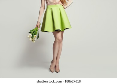 women legs with nude shoes, skirt and flowers