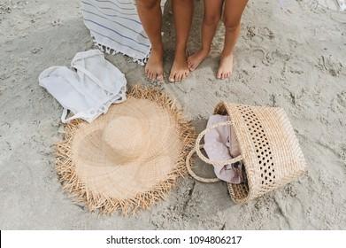 Women legs, Straw hat, bag lei garland of white sand on a sea beach.