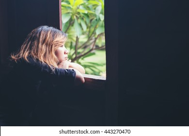Women lifestyle concept : young sad woman sitting on bench beside window look to outside, sadness,loneliness.