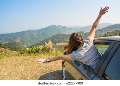 Women lifestyle enjoy with nature. woman relaxing and  raising arms out of window in a car road trip