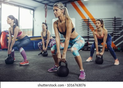 Women lifting kettlebells at gym. Group of female athletes lifting kettlebells on gym floor.