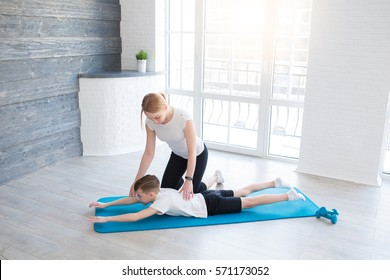 Women with little boy doing stretching workout on fitness mat. Mother with kid performing exercises at home.