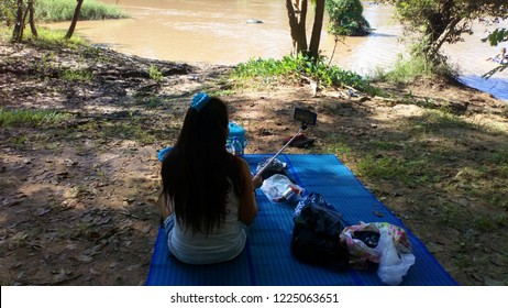 Women with long hair in white sitting picnicking, relaxing on the river....River view, natural trees