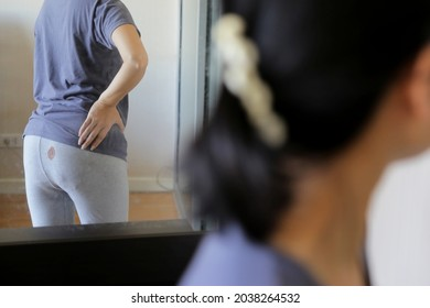 Women look at her pants with period blood spot stains on mirror with blur background. Need to be cleaned.