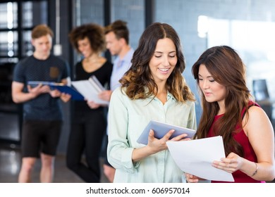 Women looking at digital tablet and having a discussion while colleagues standing behind in office