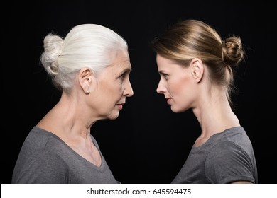 women looking at each other, young and senior people isolated on black