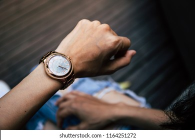 women looking at luxury watch on hand check the time.concept for managing time for organizatio of working process,punctuality,appointment.fashionable wearing stylish accessories.