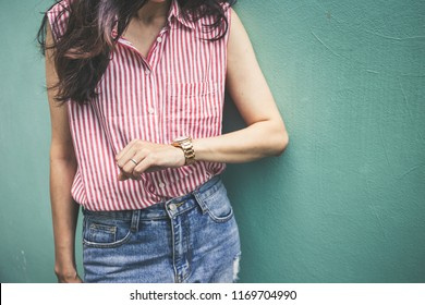women looking at luxury watch on hand check the time.concept for managing time for organization of working process,punctuality,appointment.fashionable wearing stylish accessories.
