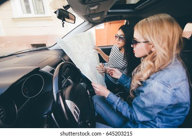 Women looking at map for directions while driving in car