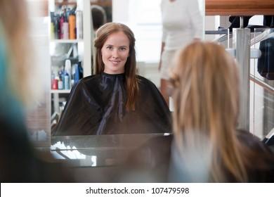 Women looking in mirror at beauty salon.