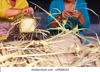 Women make baskets for balinese traditional offerings to gods in a temple, Bali, Indonesia