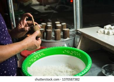 Women make Putu Bambu cakes. Kue Putu bamboo is a traditional Indonesian cake made from rice flour, brown sugar, palm sugar, and coconut.