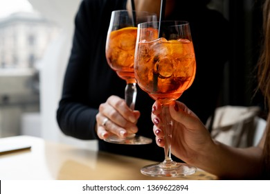 Women making a celebratory toast with aperol spritz cocktails
