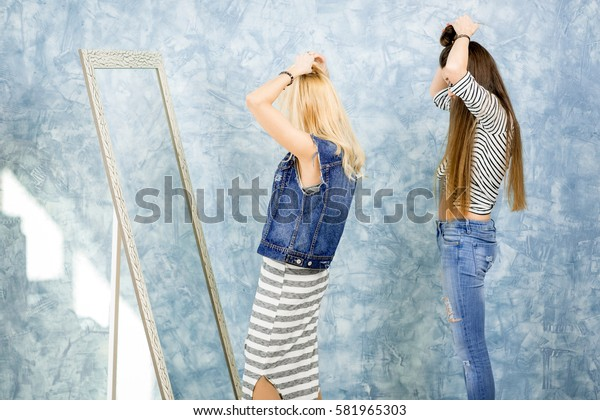 Women making hairstyle near the mirror on the blue wall background