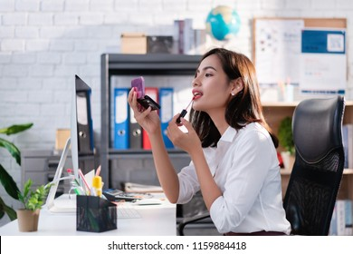 Women are making up at her office during work.