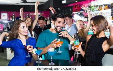 Women with man are drinking cocktails and having fun in nightclub
