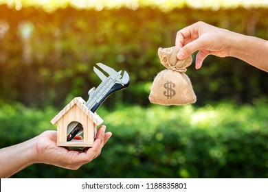 Women and man hand holding a wooden home with repairing and a money bag put together on sunlight in the public park, Saving money and loan for construction real estate and house concept.