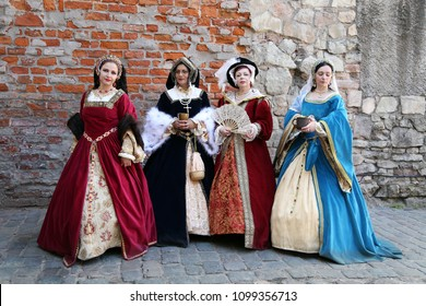 Women in medieval clothes represent  wives of King Henry VIII of England. Festival of retro costumes and historical reconstructions. History of the Middle Ages