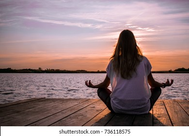 women in meditative yoga position on wooden pontoon on the lake
