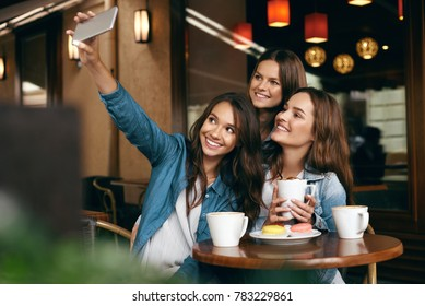 Women Meeting In Cafe. Friends Taking Photo On Phone. Beautiful Smiling Girlfriends Having Coffee Break And Taking Selfies On Mobile Phone In Coffee Shop. High Quality Image.