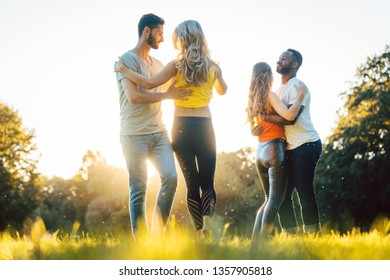 Women and men having fun dancing in the park as couples